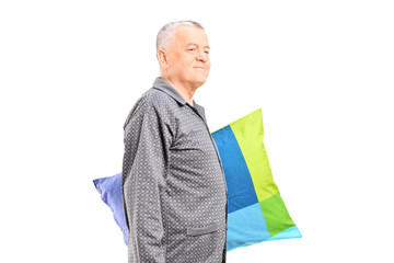Senior in pajamas walking and holding a pillow