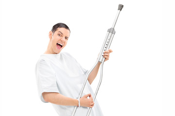 Silly patient playing on a crutch and dancing