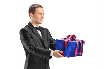 Young guy holding a present isolated on white background