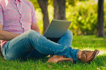 Young man sitting with Laptop Computer in the park