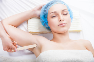 Woman getting waxing armpit by beautician