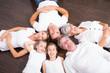 canvas print picture - familie liegend auf dem parkett