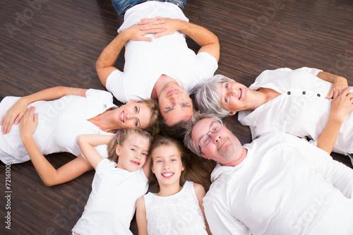 canvas print picture familie liegend auf dem parkett