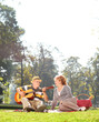 Senior playing guitar to his wife in park