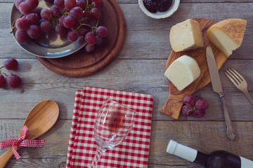 Wine, cheese and grapes on wooden table. View from above
