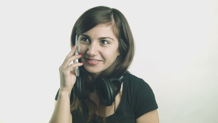Young woman with headphones talking on her smartphone