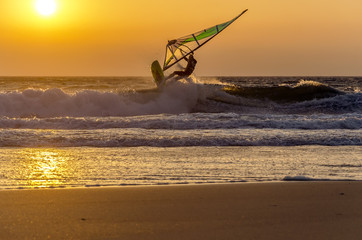 Windsurfer speeding fast against the sunset in soft focus. Summe