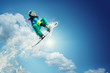 Snowboarder jumping against blue sky - 72164464