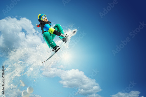 Staande foto Wintersporten Snowboarder jumping against blue sky