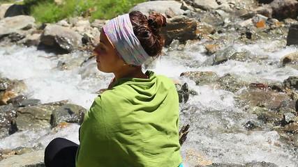 Female tourist praying near mountain river, Buddhism, relaxation