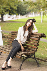 Pensive and elegant beautiful woman sitting on old bench.