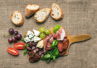 Cheese and meat platter with fresh grapes, cherry-tomatoes, oliv