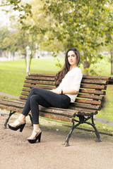 Elegant beautiful woman sitting on bench in the park.