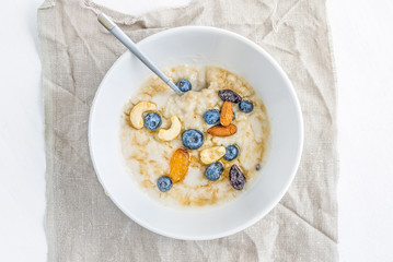 Oat porridge with fresh blueberry, nuts and honey in a white cer