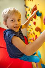 Happy boy on the climbing wall