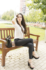 Beautiful and elegant woman sitting on bench in the park.