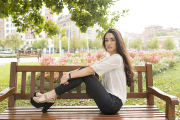 Beautiful and elegance woman sitting on bench in the park.