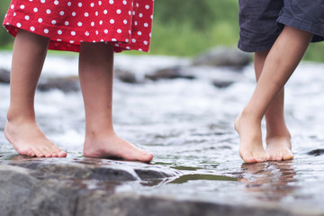 Children soaking feet in a brook