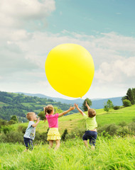 Cheerful kids playing balloon on the meadow