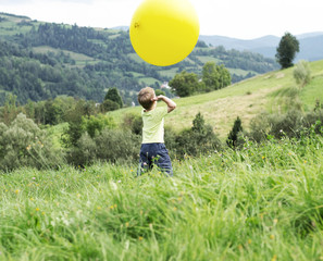 Small boy playing a huge balloon