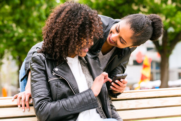Best friends chatting with smartphone on park bench