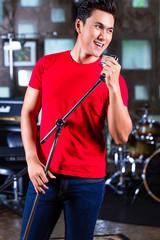 Asian singer producing song in recording studio