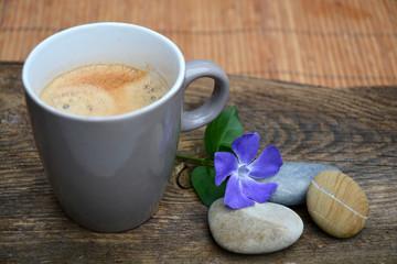 Koffie met drie zen stenen op bruin oud houd met paarse bloem