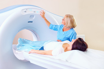 mid adult medical staff preparing patient to tomography