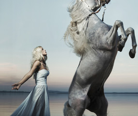 Blond nymph posing with majestic horse