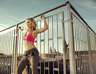 Pretty athlete doing exercises on the roof