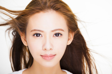 beautiful young woman face with hair motion on white background.