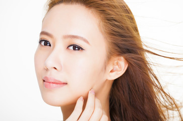 beautiful young woman face with hair motion . skin care and hair