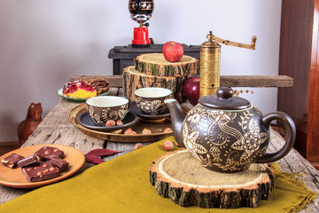 cups of tea on old wooden table, with apples and nuts