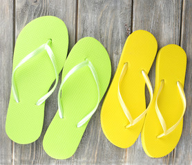 Color flip-flops on wooden board, isolated on white