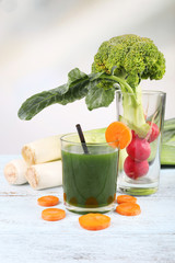 Glass of fresh vegetable juice with vegetables on wooden table