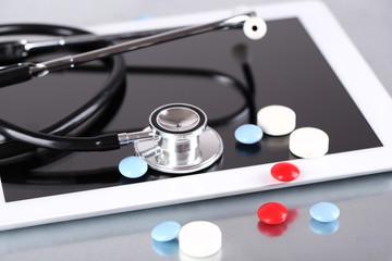 Stethoscope, pills, PC tablet