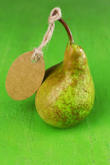 Ripe pear with paper tag on wooden background