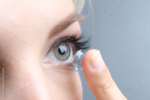 Medicine and vision concept - young woman with contact lens, - 72173074