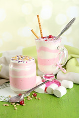 Cranberry milk dessert in glass and glass jar,