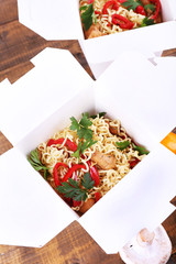 Chinese noodles in takeaway boxes on wooden background