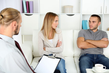 Unhappy couple not talking on couch at therapy session