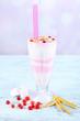 Leinwandbild Motiv Cranberry milk shake in glass, on color wooden background