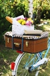 Leinwandbild Motiv Bicycle and brown suitcase with picnic set