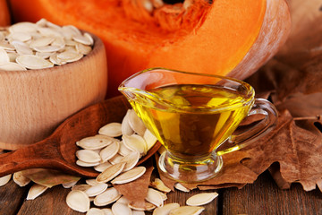 Pumpkin seed oil in glass sauce-boat and fresh pumpkin