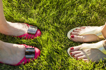 Feet of two women standing on the grass