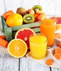 Fruit and vegetable juice in glasses and fresh fruits in box