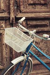Old bicycle with empty metal basket on brown door background
