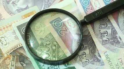 Polish zloty banknotes with magnifying glas. Full HD.
