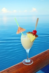 A tropical drink on a cruise ship rail with ocean in the backgro