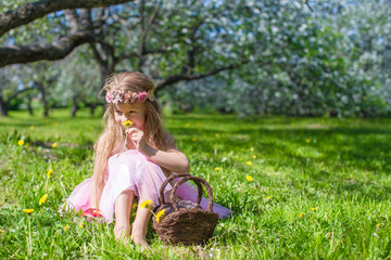 Cute little girl in blossoming apple garden at sunny spring day